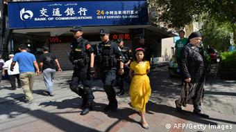 Chinese armed police patrol the streets of the Muslim Uighur quarter in Urumqi on June 29, 2013 after a series of recent terrorist attacks hit the Xinjiang region.