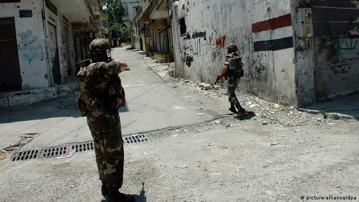 epa03763582 Syrian army soldiers patrol the streets of the Talkalkh area near the Lebanese border, in the province of Homs, Syria, 27 June 2013. More than 100,000 people have been killed in Syria's 27-month conflict, an activist group said 26 June. The Britain-based Syrian Observatory for Human Rights said it had documented the death of 100,191 people, including 50,200 civilians, in the country since March 2011. The dead also included 25,407 government troops and 169 fighters with the Lebanese Hezbollah movement, a key ally of Syrian President Bashar al-Assad. EPA/STR