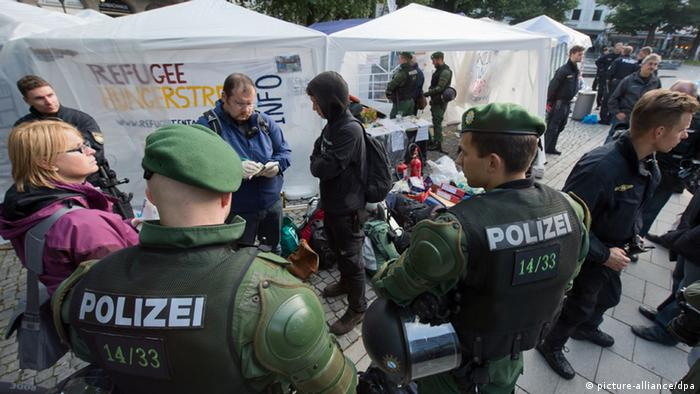 Police raid a camp occupied by aslum seekers on hunger strike in Munich on June 30, 2013. Peter Kneffel/dpa
