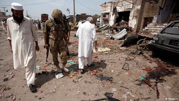 Security officials collect evidence at the site of a bomb attack in the outskirts of Peshawar on Sunday. (Photo: Fayez Aziz/Reuters)
