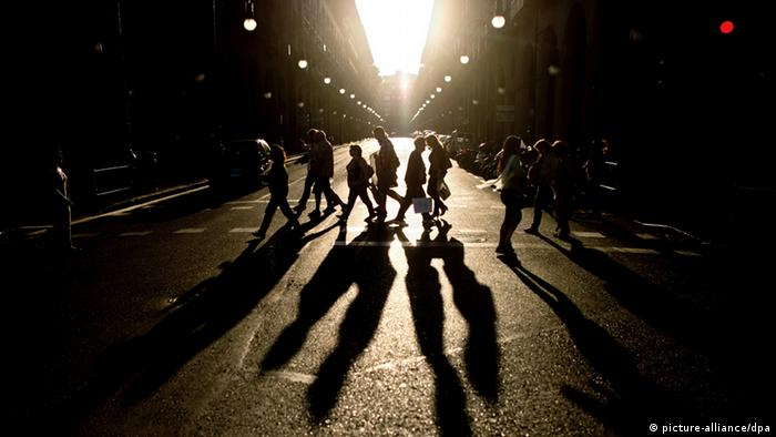 People on Mallorca cast long shadows as they cross a street Photo: Julian Stratenschulte/dpa