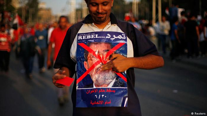 A protester opposing Egyptian President Mohamed Mursi holds an anti-Mursi poster during a protest in front of the presidential palace