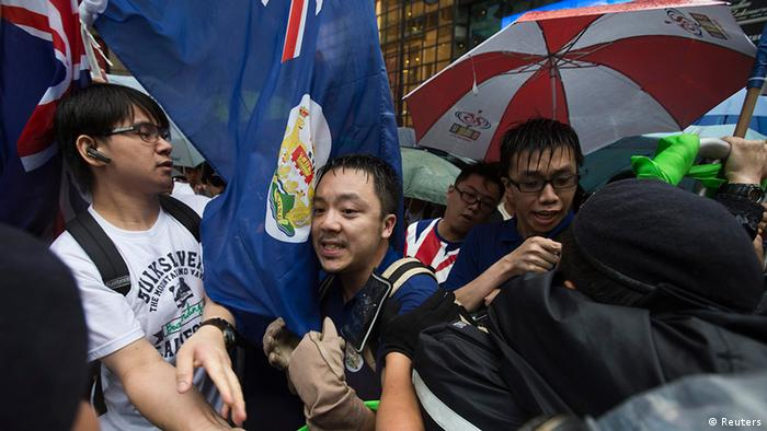 Pro-democracy protesters, with Hong Kong colonial flags, clash with police during a protest to demand universal suffrage and urge Hong Kong's Chief Executive Leung Chun-ying to step down in Hong Kong July 1, 2013. Monday marked the 16th anniversary of the territory's handover to China from Britain. REUTERS/Tyrone Siu (CHINA - Tags: POLITICS CIVIL UNREST ANNIVERSARY)