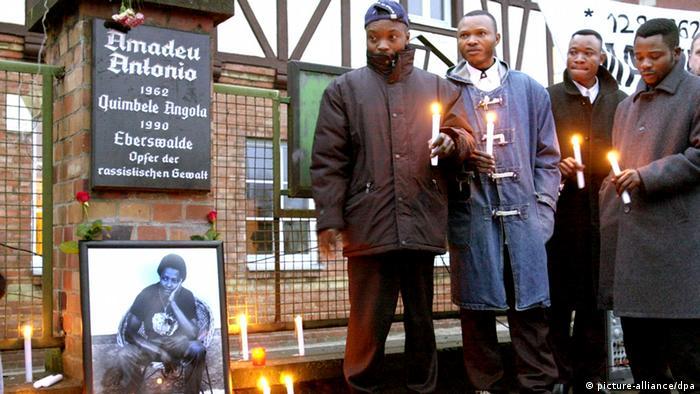 Mit Kerzen in den Händen gedenken vier Männer des von Neonazis ermordeten Amadeu Antonio in Eberswalde, 2000