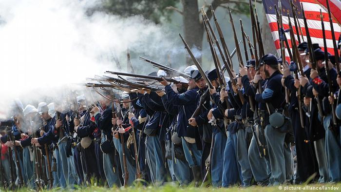 Männer in Unformen der Konföderierten Südstaaten mit Gewehren stehen in eienr Linie nebeneinander, man sieht Pulverrauch