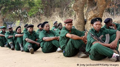 RENAMO soldiers in green uniforms and berets sit seated in a row