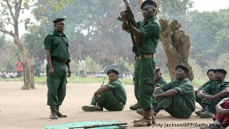 A group of soldiers in green uniform holding assault rifles.