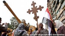 Zu: Bericht zur Religionsfreiheit von Christen weltweit Ein koptisch christlicher Demonstrant hält im Schutz des Militärs, das mit Panzern angerückt ist, bei einer Demonstration vor dem staatlichen TV-Gebäude in Kairo ein Kreuz und eine ägyptische flagge in der Hand (Archivaufnahme vom 11.3.2011). Die Christen fordern mehr Rechte im neuen Ägypten.