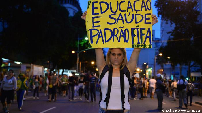 A demonstrator displays a banner for better education during a protest in a street near the Maracana stadium of Rio de Janeiro on June 30, 2013, a few hours before the final of the Fifa Confederations Cup football tournament between Brazil and Spain. More than 11,000 police and troops were mobilised in the city to guarantee security for 78,000 fans at the venue as the curtain falls on a competition that has been beset by social unrest with more than 1.5 million people taking to the streets across the giant nation in the past two weeks. AFP PHOTO / YASUYOSHI CHIBA (Photo credit should read YASUYOSHI CHIBA/AFP/Getty Images)