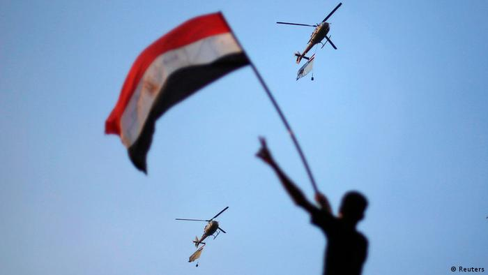 Egyptian military helicopters trailing national flags circled over Tahrir Square during a protest demanding that Egyptian President Mohamed Mursi resign in Cairo July 1, 2013. Five Egyptian military helicopters trailing national flags circled over Cairo on Monday after the armed forces gave politicians 48 hours to resolve a crisis over calls for the resignation of Islamist President Mohamed Mursi. REUTERS/Suhaib Salem (EGYPT - Tags: POLITICS CIVIL UNREST MILITARY TPX IMAGES OF THE DAY)