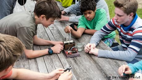 A group of young boys sit around a metal steam machine and wait for something to happen. (Foto: DW/Klaus Esterluß)