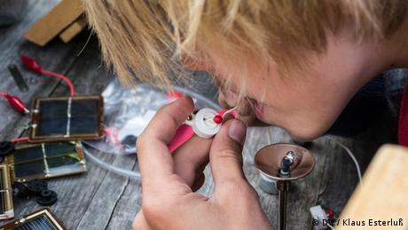 A young boy works intently on a white and red switch. In the background, small solar panels. (Foto: DW/Klaus Esterluß)