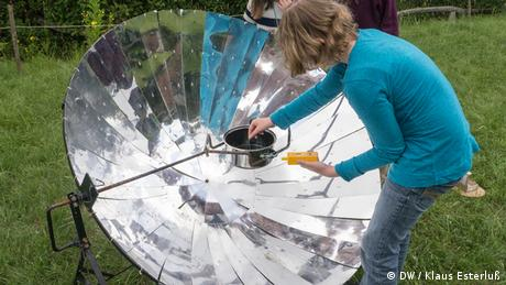 Three girls stand around a solar cooker where a metal, reflecting pot is warming up on the ground. The Ökowerk's building is just behind them. (Foto: DW/Klaus Esterluß)