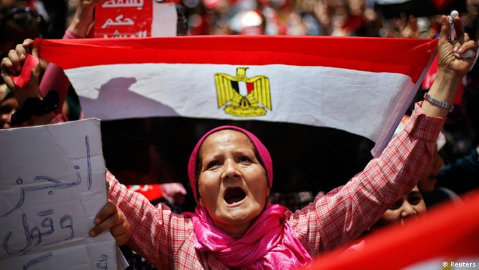 A protester, opposing Egyptian President Mohamed Mursi, holds up Egypt's flag during a protest demanding that Mursi resign at Tahrir Square in Cairo July 2, 2013. Egypt's army reprised its role as hero in a new act of the country's political drama on Monday with a move celebrated by protesters as a decisive blow against an unpopular president just two and half years after the military unseated his predecessor. REUTERS/Suhaib Salem (EGYPT - Tags: CIVIL UNREST POLITICS TPX IMAGES OF THE DAY)