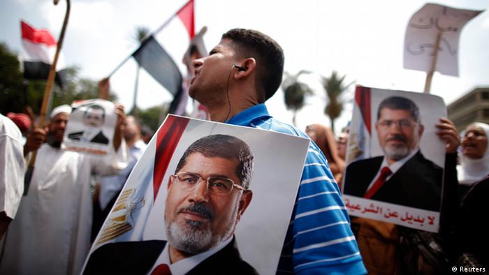 Supporters of Egypt's President Mohamed Mursi hold posters of him during a protest to show their support for him near Cairo University July 2, 2013. Mursi rebuffed an army ultimatum to force a resolution to Egypt's political crisis, saying on Tuesday that he had not been consulted and would pursue his own plans for national reconciliation. REUTERS/Khaled Abdullah (EGYPT - Tags: POLITICS CIVIL UNREST)