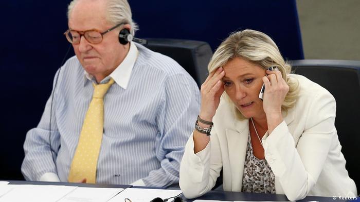 Marine Le Pen (R), France's far-right National Front political party leader, speaks on the phone as she attends a voting session at the European Parliament beside her father Jean-Marie Le Pen in Strasbourg, July 2, 2013. The leader of France's far-right National Front lost her right to legal immunity as a European Parliament deputy on Tuesday, exposing her to possible prosecution over a racism charge. Marine Le Pen's loss of immunity came at the request of a Lyon court three years after she was accused of inciting racial hatred for comparing Muslim street prayers to the occupation of France by Nazi Germany. REUTERS/Vincent Kessler (FRANCE - Tags: POLITICS)
