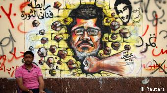 A protester, opposing Egypt's President Mohamed Mursi, sits next to graffiti depicting Mursi on a wall of the Presidential Palace REUTERS/Khaled Abdullah