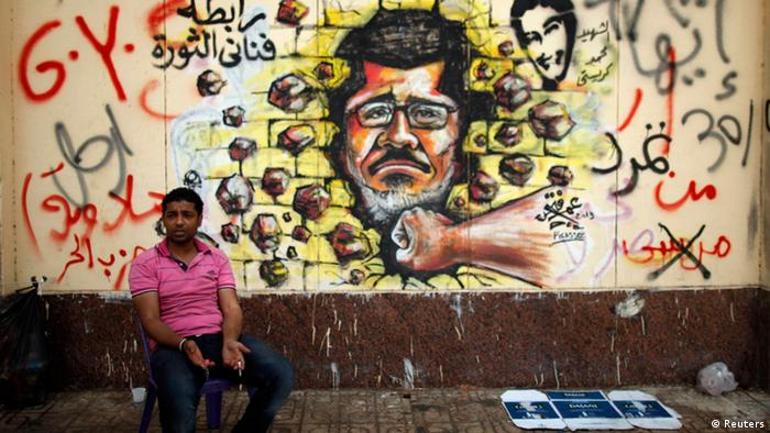 A protester, opposing Egypt's President Mohamed Mursi, sits next to graffiti depicting Mursi on a wall of the Presidential Palace in Cairo July 2, 2013. Egypt's justice minister denied an al-Arabiya television report that the government had resigned on Tuesday after the armed forces gave President Mohamed Mursi 48 hours to agree to share power in response to mass protests. REUTERS/Khaled Abdullah (EGYPT - Tags: POLITICS CIVIL UNREST)