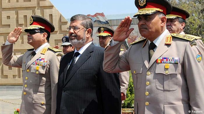 Egypt's President Mohamed Mursi (C) stands after laying a wreath during his visit to the tomb of former President Anwar al-Sadat and the Tomb of the Unknown Soldier during the commemoration of Sinai Liberation Day in Cairo, in this April 24, 2013 file photograph. Saluting next to Mursi are Egypt's Defence Minister Abdel Fattah al-Sisi (L) and General Sedki Sobhi (R), chief of staff to Egypt's Supreme Council of the Armed Forces (SCAF). To match Newsmaker EGYPT-PROTESTS/COMMANDER REUTERS/Egyptian Presidency/Handout/Files (EGYPT - Tags: POLITICS MILITARY ANNIVERSARY) ATTENTION EDITORS - THIS IMAGE WAS PROVIDED BY A THIRD PARTY. FOR EDITORIAL USE ONLY. NOT FOR SALE FOR MARKETING OR ADVERTISING CAMPAIGNS. THIS PICTURE WAS PROCESSED BY REUTERS TO ENHANCE QUALITY