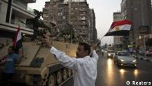 Egyptians salute army tanks upon their deployment on a street leading to Cairo University on July 3, 2013. A top aide to Egypt's President Mohamed Morsi slammed what he called a 'military coup' as an army ultimatum passed and the security forces slapped a travel ban on the Islamist leader. AFP PHOTO/KHALED DESOUKI (Photo credit should read KHALED DESOUKI/AFP/Getty Images)