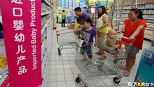 A family looks at foreign imported milk powder products at a supermarket in Beijing July 3, 2013. The decision by China's top economic planner to investigate five leading foreign infant milk companies for suspected antitrust violations may be part of a broader plan to boost consumption of the local product, analysts said on Wednesday. Mothers turned away from Chinese milk powder in 2008 when infant formula tainted with the industrial compound melamine killed at least six babies and made thousands sick with kidney stones. REUTERS/Kim Kyung-Hoon (CHINA - Tags: BUSINESS FOOD HEALTH)