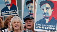 Demonstrators hold banner during protest rally in support of former U.S. spy agency NSA contractor Edward Snowden in Berlin July 4, 2013. The sentence reads: Shelter in Germany for Edward Snowden. REUTERS/Tobias Schwarz (GERMANY - Tags: POLITICS)