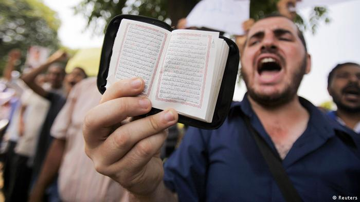 A member of the Muslim Brotherhood and supporter of ousted Egyptian President Mohamed Mursi holds a copy of the Koran while shouting slogans during the swearing in ceremony of the head of Egypt's Constitutional Court Adli Mansour as the nation's interim president in Cairo July 4, 2013. Egypt's prosecutor ordered the arrest of the Muslim Brotherhood's leader on Thursday, widening a crackdown against the Islamist movement after the army ousted the country's first democratically elected president Mursi. But Adli Mansour used his inauguration to hold out an olive branch to the Brotherhood. REUTERS/ Amr Abdallah Dalsh (EGYPT - Tags: POLITICS CIVIL UNREST MILITARY RELIGION)