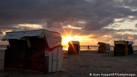 die untergehende Sonne am Strand