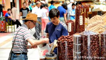 A tourist buys various local produce at the city bazaar in Urumqi, farwest China's Xinjiang region on July 5, 2013. (Photo: AFP)