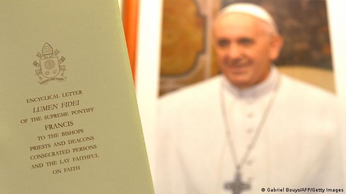 Papst Franziskus mit der ersten Enzyklika 'Lumen Fidei' Foto: AFP PHOTO / GABRIEL BOUYS