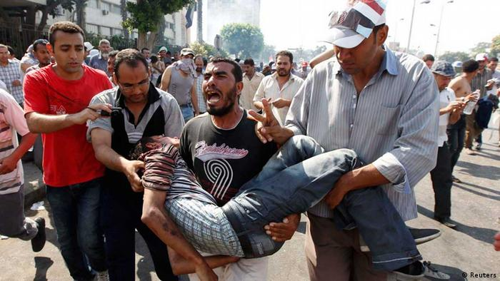 Protesters carry an injured man during clashes REUTERS/Louafi Larbi