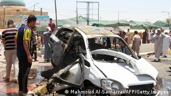 Iraqis inspect the site of a suicide car bomb attack (Photo:MAHMOUD AL-SAMARRAI/AFP/Getty Images)