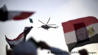 An Egyptian military helicopter hovers over supporters of the Muslim Brotherhood during a rally in support of deposed president Mohamed Morsi outside Cairo's Rabaa al-Adawiya mosque on July 5, 2013. Supporters of ousted Egyptian president Mohamed Morsi took to the streets in their tens of thousands, defying his army deposers and triggering running clashes that killed at least three people. AFP PHOTO/MAHMUD HAMS (Photo credit should read MAHMUD HAMS/AFP/Getty Images)