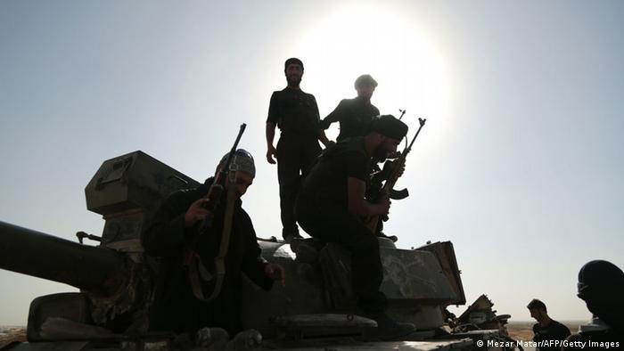 Syrische Rebellen inspizieren einen Tank. . Foto: AFP/Getty Images)