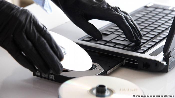 Person with black gloves on at computer keyboard