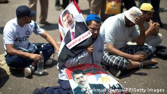 Egyptian supporters of the Muslim Brotherhood sit during a rally in support with deposed president Mohamed Morsi (featured on the posters) on July 6, 2013 outside Cairo's Rabaa al-Adawiya mosque. Egypt's Islamists vowed further protests today to demand the army restore the country's first democratically elected leader, after a day of clashes which saw 26 people killed across the country. AFP PHOTO/MAHMUD HAMS (Photo credit should read MAHMUD HAMS/AFP/Getty Images)