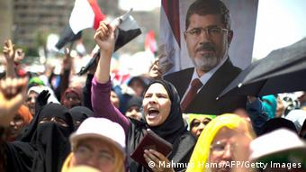 Egyptian supporters of the Muslim Brotherhood shout slogans during a rally in support with deposed president Mohamed Morsi (featured on the poster) on July 6, 2013 outside Cairo's Rabaa al-Adawiya mosque. Egypt's Islamists vowed further protests today to demand the army restore the country's first democratically elected leader, after a day of clashes which saw 26 people killed across the country. AFP PHOTO/MAHMUD HAMS (Photo credit should read MAHMUD HAMS/AFP/Getty Images)