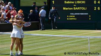 Marion Bartoli of France (R) embraces Sabine Lisicki of Germany after defeating her in their women's singles final tennis match at the Wimbledon Tennis Championships, in London July 6, 2013. REUTERS/Toby Melville (BRITAIN - Tags: SPORT TENNIS)