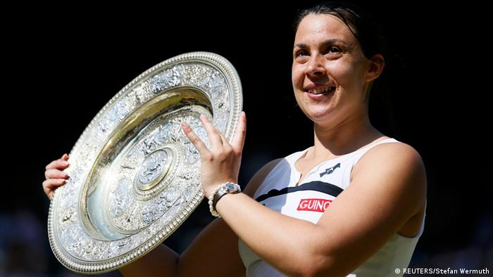 Marion Bartoli of France holds her trophy, the Venus Rosewater Dish, after defeating Sabine Lisicki of Germany in their women's singles final tennis match at the Wimbledon Tennis Championships, in London July 6, 2013. REUTERS/Stefan Wermuth (BRITAIN - Tags: SPORT TENNIS TPX IMAGES OF THE DAY)