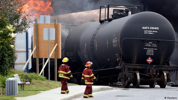 Firefighters walk past a burning train wagon after an explosion at Lac Megantic, Quebec, July 6, 2013. REUTERS/Mathieu Belanger (CANADA - Tags: DISASTER SOCIETY)
