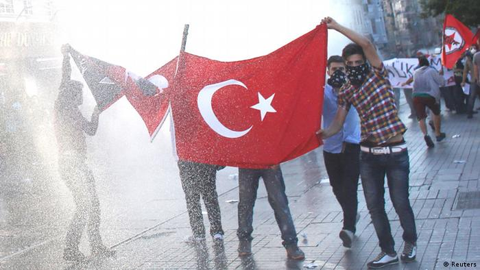 Protesters hold a Turkish flag on Taksim square