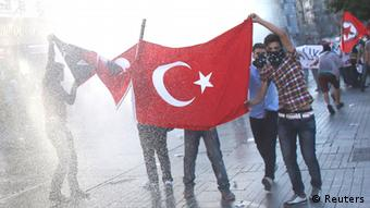 Protesters hold a Turkish flag as riot police use a water cannon to disperse them. Copyright: REUTERS/Murad Sezer