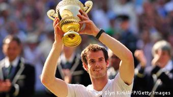 Britain's Andy Murray raises the winner's trophy after beating Serbia's Novak Djokovic in the men's singles final on day thirteen of the 2013 Wimbledon Championships tennis tournament at the All England Club in Wimbledon, southwest London, on July 7, 2013. Murray won 6-4, 7-5, 6-4. AFP PHOTO / GLYN KIRK - RESTRICTED TO EDITORIAL USE (Photo credit should read GLYN KIRK/AFP/Getty Images)