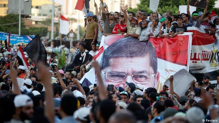 Supporters of ousted Egyptian President Mohamed Mursi chant slogans while carrying a big banner of Mursi in front of the Republican Guard headquarters as they camp for the third day in Cairo July 7, 2013. Thousands of supporters of Mursi protested outside his place of detention in Cairo on Sunday while a military-driven plan to resolve the political crisis remained mired in mistrust and confusion. REUTERS/Asmaa Waguih (EGYPT - Tags: POLITICS CIVIL UNREST MILITARY)