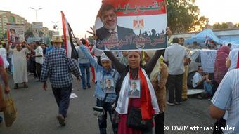 A woman holds up a banner with the portrait of Mohammed Morsi Photo: DW/Matthias Sailer