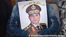 An Egyptian man holds portrait of defense minister Abdelfatah el-Sisias as they gather in Cairo's Tahrir Square on July 7, 2013. Opponents of Egypt's deposed Islamist president Mohamed Morsi packed Tahrir Square in their tens of thousands to show the world his ouster was not a military coup but the reflection of the people's will. AFP PHOTO / KHALED DESOUKI (Photo credit should read KHALED DESOUKI/AFP/Getty Images)
