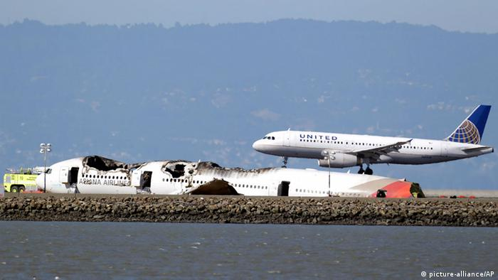 A United Airlines plane lands next to the wreckage of Asiana Flight 214 at the San Francisco International Airport in San Francisco, Sunday, July 7, 2013. (AP Photo/Marcio Jose Sanchez)