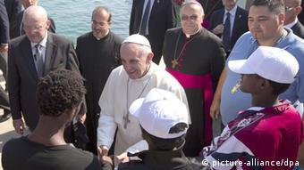 Pope Francis speaks to migrants during his visit to the island of Lampedusa