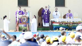 Pope Francis, holding with a cross made from the wood of rickety fishing boats that migrants typically arrive on, leaves after leading a mass during his visit to the island of Lampedusa, a key destination of tens of thousands of would-be immigrants from Africa, on July 8, 2013. Pope Francis called for an end to 'indifference' to the plight of refugees on Monday on a visit to an Italian island where tens of thousands of migrants from Africa and the Middle East first reach Europe. AFP PHOTO / ANDREAS SOLARO (Photo credit should read ANDREAS SOLARO,ANDREAS SOLARO/AFP/Getty Images)