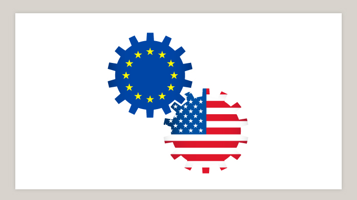 Two gears bearing the EU and US flags connect